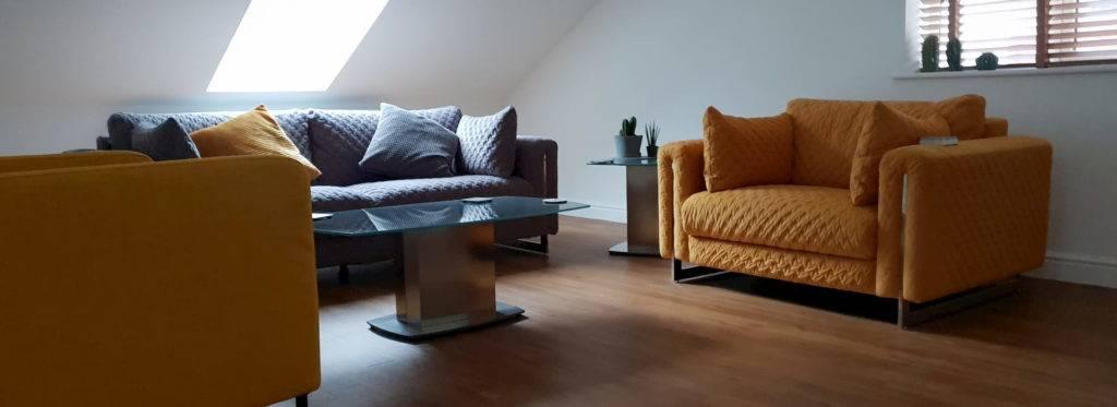 Inside furnished loft conversion blue and orange sofas